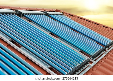 Vacuum collectors- solar water heating system on red roof of the house under shining sun