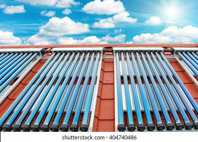 Vacuum collectors- solar water heating system on red roof of the house. Sun rays, blue sky with white clouds above