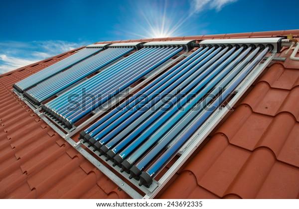 Vakuumsammler- solare Wasserheizung auf rotem Dach des Hauses.