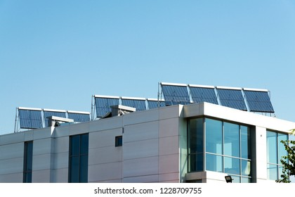 Vacuum solar cell for water heating system on the modern building roof. Green energy, alternative heating and energy supply systems. Ecologically clean energy of sunlight