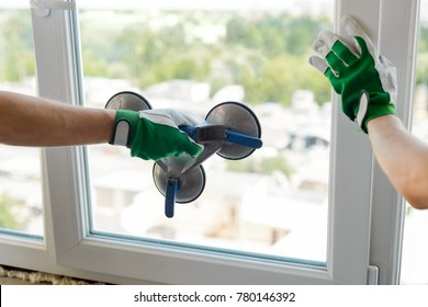 Vacuum suction lifter. Hand holding a special tool for carrying a glass pane. Window installation process.