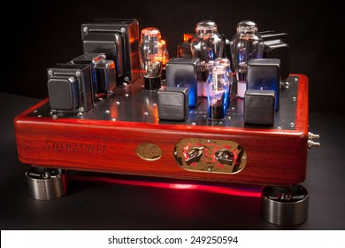 Vacuum tube stereo amplifier : Hi end power amplifier with wood chassis and carbon fiber plate in a black background