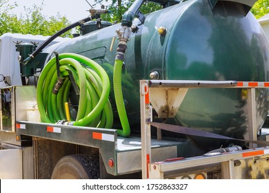 Vacuum waste truck on the cleaning process portable bio toilet cabins at the construction