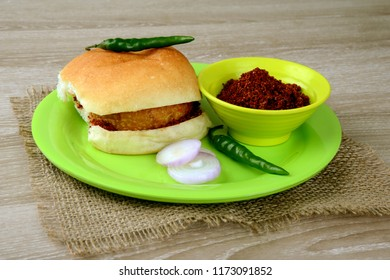 Vada Pav, a delicious and popular street food with onion slice, green chili and garlic chutney