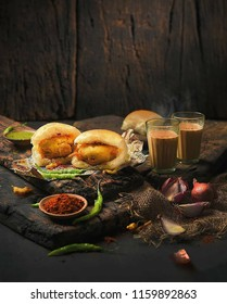 Vada Pav, dish consists of a deep fried potato dumpling placed inside a bread bun (pav) sliced almost in half through the middle. A picture of vada pav and with chai