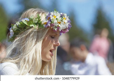VADDO, SWEDEN - JUNE 23, 2017: Blonde woman with flowers in her hair preparing to celebrate the Swedish Midsummer in Sweden, June 23, 2017