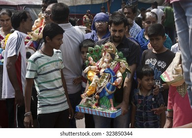 VADODARA, GUAJARAT / INDIA - SEPTEMBER 27, 2015 : A MAN IS HOLDING ON HIS HAND THE STATUE OF A HINDU GOD SHREE GANESHA TO DISSOLVE IT INTO THE WATER AS PART OF THE RITUAL CEREMONY.