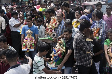VADODARA, GUAJARAT / INDIA - SEPTEMBER 27, 2015 : PEOPLE ARE STANDING WITH HOLDING ON THEIR HAND THE STATUE OF A HINDU GOD SHREE GANESHA TO DISSOLVE IT INTO THE WATER AS PART OF THE RITUAL CEREMONY.