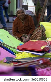 VADODARA, GUJARAT / INDIA - JANUARY 12, 2017 : A SALES WOMAN SELLING KITES AT THE STREET MARKET, BEFORE THE KITE FESTIVAL DAY IN INDIA.