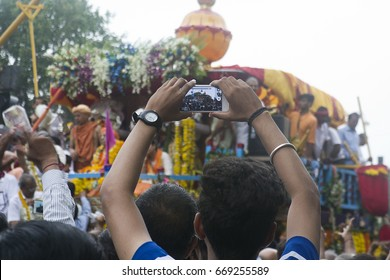 VADODARA, GUJARAT / INDIA - JUNE 25, 2017 : BACK VIEW OF A MAN TAKING A PHOTOGRAPH OF THE CHERIOT DURING THE FESTIVAL IN VADODARA, INDIA.