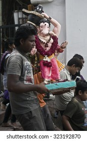 VADODARA, GUJARAT / INDIA - SEPTEMBER 27, 2015 : PEOPLE  ARE TAKING THE STATUE OF A HINDU GOD SHREE GANESHA TO THE POND TO DISSOLVE OR SUBMERGE IT INTO THE WATER AS PART OF THE RITUAL CEREMONY.