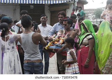 VADODARA, GUJARAT / INDIA - SEPTEMBER 5, 2017 : A FAMILY WITH THE STATUE OF A LORD SHREE GANESHA DURING THE GANESHA FESTIVAL.