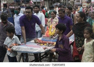 VADODARA, GUJARAT / INDIA - SEPTEMBER 5, 2017 : THE STATUE OF A HINDU GOD SHREE GANESHA SETTING ON A HAND CARD AND PULLED BY THE FAMILY DURING THE GANESHA FESTIVAL.