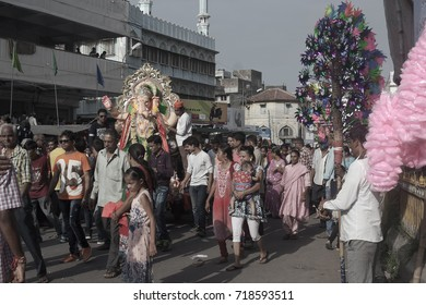 VADODARA, GUJARAT / INDIA - SEPTEMBER 5, 2017 : POEPLE ARE TAKING THE STATUE OF A LORD SHREE GANESHA TO THE LAKE TO SUBMERGE IT INTO THE LAKE WATER DURING THE GANESHA FESTIVAL.