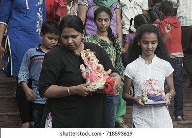 VADODARA, GUJARAT / INDIA - SEPTEMBER 5, 2017 : A YOUNG GIRL AND A WOMAN WITH THEIR LITTLE STATUE OF LORD SHREE GANEHSA CARRYING ON THEIR HANDS DURING THE GANESHA FESTIVAL.