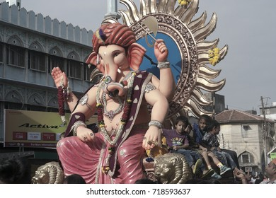 VADODARA, GUJARAT / INDIA - SEPTEMBER 5, 2017 : A BIG STATUE OF A LORD SHREE GANESHA AND THE LITTLE CHILDREN ARE SITTING BESIDES THE STATUE DURING THE GANESHA FESTIVAL.