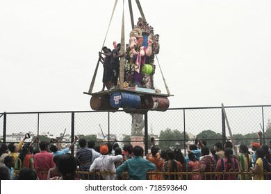 VADODARA, GUJARAT / INDIA - SEPTEMBER 5, 2017 : A BIG STATUE OF A LORD SHREE GANESHA CARRIED AWAY BY THE CRANE AND TAKING IT INTO THE LAKE WATER TO SUBMERGE IT INTO WATER DURING THE GANESHA FESTIVAL.