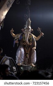 VADODARA, GUJARAT / INDIA - SEPTEMBER 5, 2017 : A STATUE OF A LORD SHREE GANESHA HUNG THROUGH THE CHAIN OF THE CRANE TO SUBMERGE INTO THE LAKE WATER DURING THE GANESHA FESTIVAL