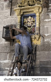 VADODARA, GUJARAT / INDIA - SEPTEMBER 5, 2017 : A MAN IS TAKING A PHOTOGRAPH WHILE SIITING ON LADER AND THE STATUE OF A LORD SHREE GANESHA BEHIND HIM DURING THE GANESHA FESTIVAL
