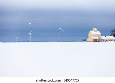 VADSTEN, SWEDEN, FEBRUARY 2015, wind turbines in a frozen landscape with a yellow barn to the side and dramatic clouds in the background.
