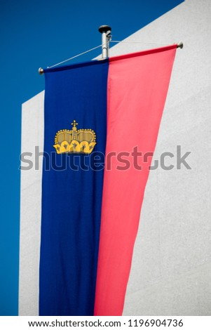 Vaduz, Liechtenstein, 16th August 2018:- The national flag of Liechtenstein flying in the capital city of Vaduz