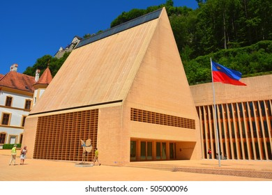 VADUZ, LIECHTENSTEIN - JUNE 30, 2015. The Parliament building in Vaduz, with flag, sculptures and people.