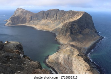 VAEROY, NORDLAND COUNTY / NORWAY - APRIL 26 2020: Mountain ridge of Vaeroy island.  Scenic coastal cliffs on island of Vaeroy, Lofoten islands in Norway. Mastadfjellet (Måstadfjellet) natural reserve