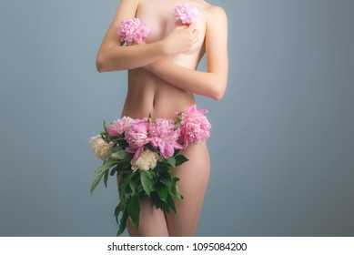 Vagina and female breast under flowers. Naked body and sexy woman. Bra and panties concept. Flowers on the body of a young sensual girl. White skin and pink flowers. Body art. Beautiful female figure