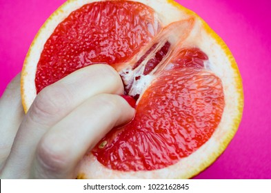 Vagina symbol. Two fingers on grapefruit on pink background. Sex concept.