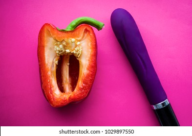 vagina symbol-sweet red pepper and purple vibrating sex toy a pink background. Concept masturbation
