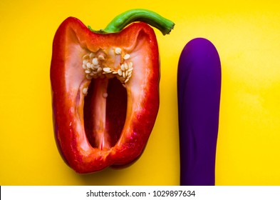 vagina symbol-sweet red pepper and purple vibrating sex toy a yellow background. Concept masturbation