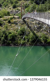 Vagli, Apuan Alps, Lucca, Tuscany. Italy.  07/09/2017. Suspended pedestrian bridge with steel cables. The bridge crosses the artificial lake of Vagli.