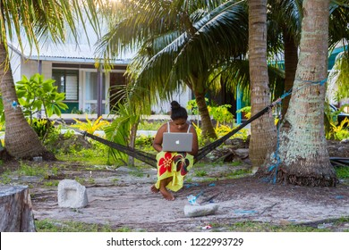 Vaiaku, Tuvalu - Dec 27, 2014: Young Polynesian woman in a hammock with a notebook working outdoors under palm trees. Tuvalu, Polynesia, South Pacific Ocean, Oceania. .tv domain concept.