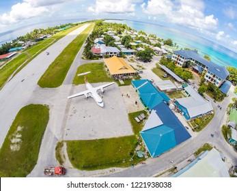 Vaiaku village, Tuvalu - Dec 27, 2014: An airplane on the apron of Tuvalu international airport, just arrived. Fongafale motu, Funafuti atoll, Polynesia, South Pacific Ocean, Oceania. Aerial view.