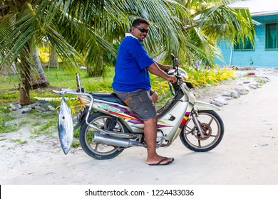 Vaiaku village, Tuvalu - Dec 27, 2014: A local native Polynesian man on a motorcycle (motorbike) with a tuna fish catch. Fongafale motu, Funafuti atoll, Polynesia, South Pacific Ocean, Oceania.
