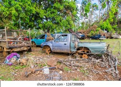 Vailala, Wallis and Futuna - Jan 6 2013: Automotive graveyard, car cemetery yard, abandoned car junkyard under palm trees on a remote island of Uvea, Wallis and Futuna. Ecological problems of islands.