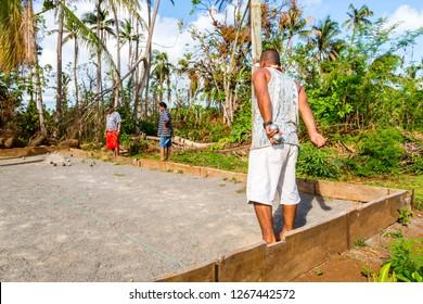 Vailala, Wallis and Futuna - Jan 6 2013: Indigenous aboriginal Polynesian people are playing petanque in French overseas collectivity Wallis et Futuna. Uvea island. Men wearing skirts lavalava.