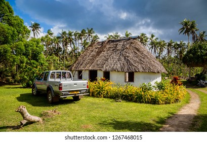 Vailala, Wallis and Futuna - Jan 6 2013: Typical rural cottage in Wallis resembles traditional thatched roof Polynesian fale. French overseas collectivity of Wallis et Futuna. Pickup car. Uvea island.
