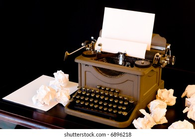 A vaintage typewriter with several wadded up pieces of paper arranged around it.  symbol of writer's block or difficulty with creativity