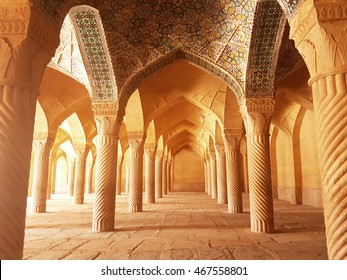 """Vakil"" mosque praying hall with spiral pillars of stones and roof tiling illuminated with sunlight located in Shiraz; Iran"