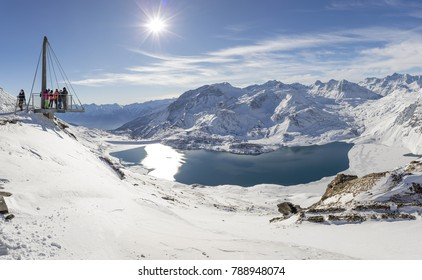VAL CENIS, FRANCE - DECEMBER 31, 2017 : People enjoying views of Mont Cenis lake and the surrounding mountains from the platform on the Col de la Met, a mountain pass in the French Alps
