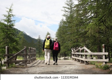 Val d'Aosta, Italy, July 4 2018: couple of elderly people view from behind walking on a wooden bridge on the mountain