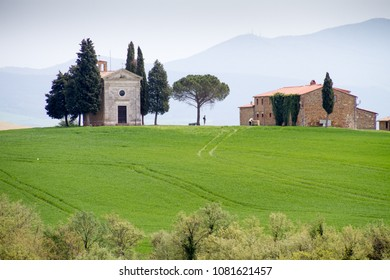 """Val d'Orcia, April 2018: Iconic Chapel """"Vitaleta"""" in Senese clays landscape with hill and cypress, on April 2018 in Val d'Orcia, Siena, Tuscany, Italy"""