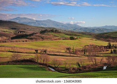 Val d'Orcia, Siena, Tuscany, Italy - April 5, 2019: spring landscape at sunset of the Val d'Orcia  countryside, the colorful hills and the Mount Amiata on background