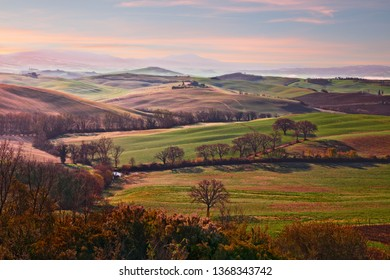 Val d'Orcia, Siena, Tuscany, Italy - April 6, 2019: landscape at sunrise of the Val d'Orcia countryside and the picturesque colorful hills