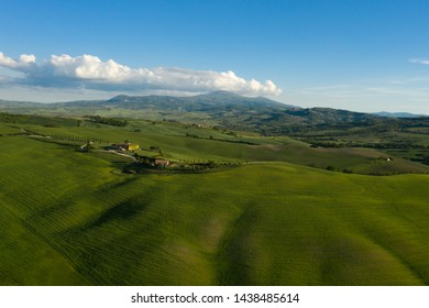 Val d'Orcia, Tuscany, Italy - May 14, 2019: Aerial view of the Italian countryside in spring before sunset.