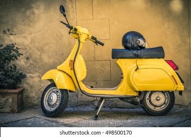 Val d'Orcia, Tuscany, Italy - May 5, 2012: Yellow Vespa scooter parked in a town in Val d'Orcia, Tuscany, Italy. Scooters are popular because are cheap to buy, easy to operate and convenient to park.