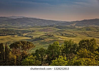 Val d'Orcia, Tuscany/Italy - May 10 2016: Scenic Tuscany landscape panorama in sunset with rolling hills and harvest fields, Val d'Orcia. View of valley Val D`Orcia on sunset.