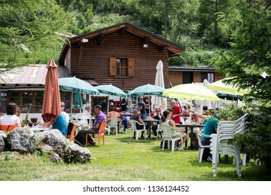Val Ferret, Courmayeur, Italy - 14 July, 2018: tourists and hikers enjoy the warm weather eating outdoor in a crowded wooden mountain refuge chalet restaurant.