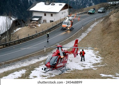 VAL GARDENA, ITALY - JANUARY 20, 2015: Two Helicopters ready to take off to save and transport a seriously injured person to hospital after hard car accident on the iced road on January 20, 2015